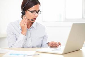 mooie Latijns-werknemer praten over een koptelefoon foto