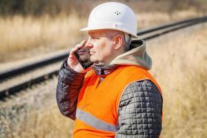 spoorwegmedewerker die op celtelefoon dichtbij spoorweg spreekt