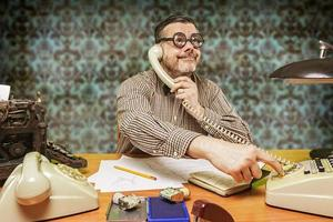 werknemer met een bril praten aan de telefoon op kantoor foto