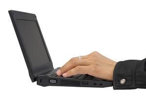 werknemershanden die met laptop werken die over witte pagina wordt geïsoleerd