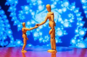 twee houten pop, mannequin of man beeldje schudden elkaar de hand