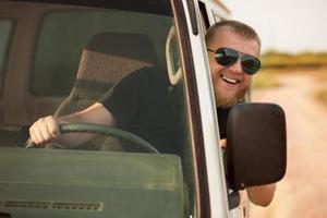 vrolijke chauffeur achter het stuur van zijn auto foto