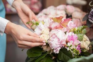 succesvolle jonge bloemist werkt in haar bloemenwinkel foto