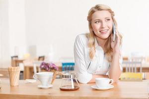 mooie jonge serveerster praten per mobiele telefoon