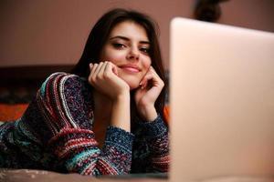 vrouw liggend op het bed met laptop foto