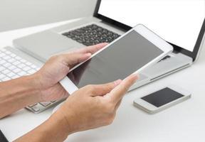 man hand met tablet pc met laptop achtergrond foto