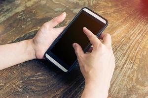 sluit omhoog van handenvrouw gebruikend telefoon in koffiewinkel foto