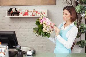 aantrekkelijke jonge verkoopster werkt in bloemenwinkel foto