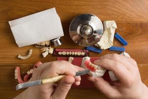 werkplek van de tandtechnicus met handen foto