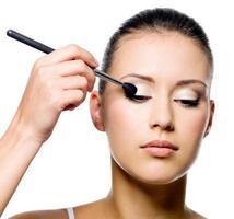 vrouw die oogschaduw met borstel toepast foto
