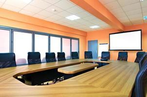 vergaderruimte met lege stoelen en een projectiescherm foto