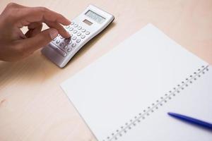 hand met rekenmachine aan balie foto