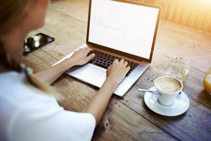 handen van de vrouw toetsenbording op net-boek zittend in café foto