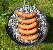 het grillen van worstjes op de barbecue foto