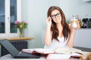 gelukkige jonge vrouw die in keuken bestudeert foto