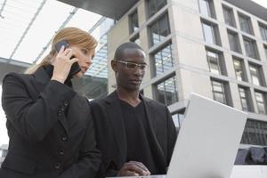 zakenman en vrouw die op een laptop werkt.