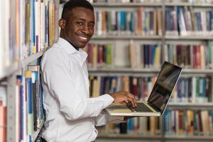 jonge student met behulp van zijn laptop in een bibliotheek foto