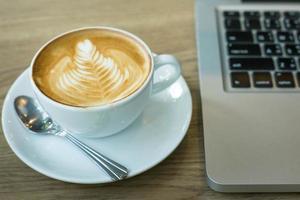 hete kunst latte koffie in een beker op houten tafel foto