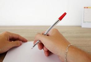 man schrijft op het papier met pen foto