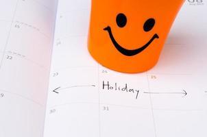 een gelukkig pictogram op de kalender met vakantietekst foto