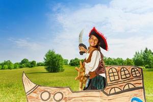 gelukkig Afrikaans meisje als piraat met hoed en zwaard foto
