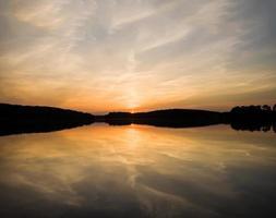 prachtige zonsondergang over kalm meer foto