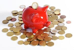 rode spaarvarken omgeven door munten foto
