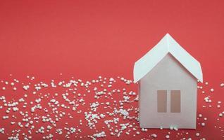 papier huis in sneeuw op rode achtergrond foto