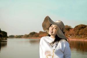 Aziatische vrouw die lacht in het park aan de kant van het meer