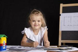 meisje-architect zit achter bureau en kijkt in frame foto