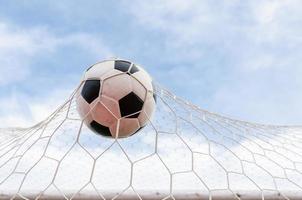 voetbal voetbal in doel net met de hemel veld. foto