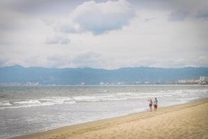 jong koppel wandelen op het strand, Pacifische kust, Mexico foto