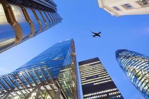 jet vliegtuig silhouet met zakelijke kantoorgebouw torens achtergrond foto