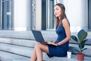 mooie jonge vrouw werkt met een notebook foto