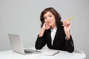 jonge mooie vrouw die met behulp van laptop werkt en in notitieboekje schrijft foto