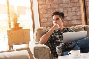 zakenman die laptop op bank in koffiewinkel met behulp van foto