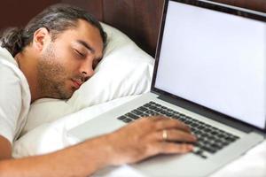 freelancer man met laptop in de ochtend emotioneel zijn bed foto