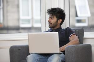 Aziatische man thuis met behulp van een laptop. foto