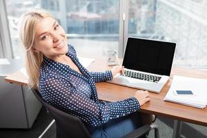 blonde aantrekkelijke vrouw die laptop met behulp van foto