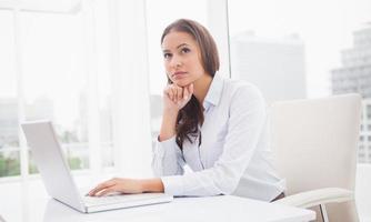 doordachte zakenvrouw met behulp van laptop op haar bureau foto