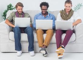 knappe ontwerpers die met laptops werken foto