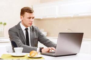 man in pak bezig met computer keuken foto