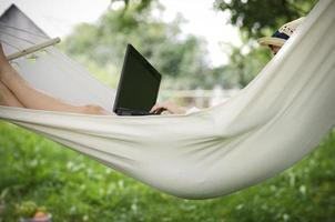 persoon zit in een hangmat tijdens het werken op een laptop foto