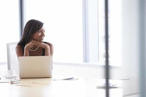 zakenvrouw die op laptop werkt aan boardroom tafel