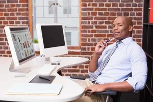 zakenman met computer bij bureau foto