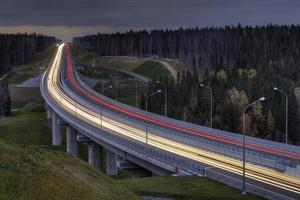 lichte paden op vierbaans snelweg, doorkruist het nachtbos. foto