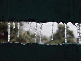 ijspegels op het balkon van de bevroren winter foto
