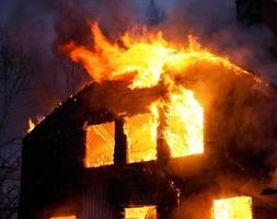 een houten huis in vlammen in het donker van de nacht foto