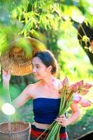 Azië oude jonge vrouw met lotus hoed en mand