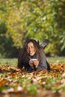 herfst in park, jonge lachende vrouw ontspannen in de natuur